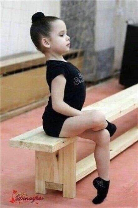 求一张图片 穿芭蕾服的外国小女孩抬头挺胸的坐在长椅上,一只脚抬图片