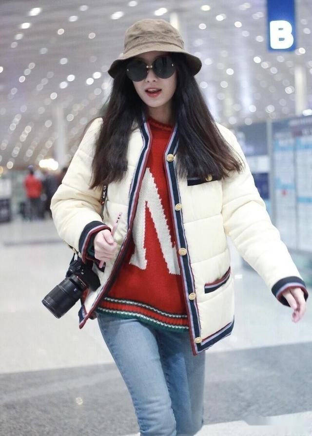 倪妮穿著低調但美得高級,短款棉服配紅色毛衣簡約保暖,舒適隨性