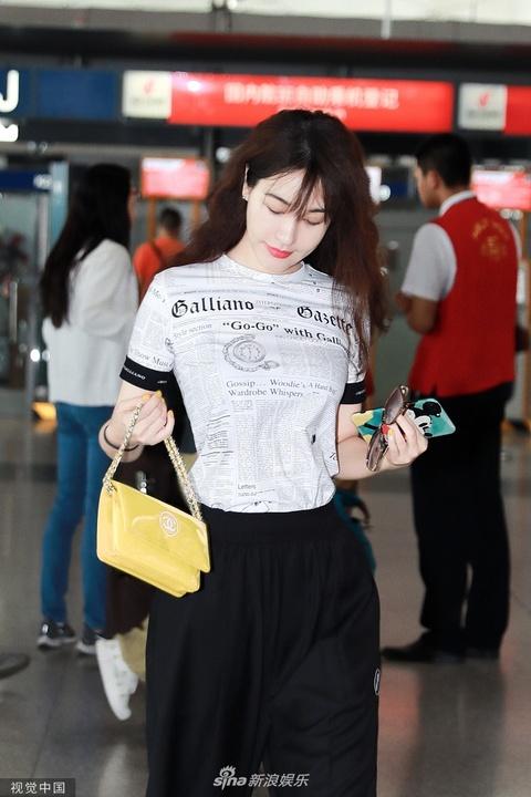 组图:李菲儿捂脸撩发女神范十足 穿报纸服拿米奇手机壳超童趣